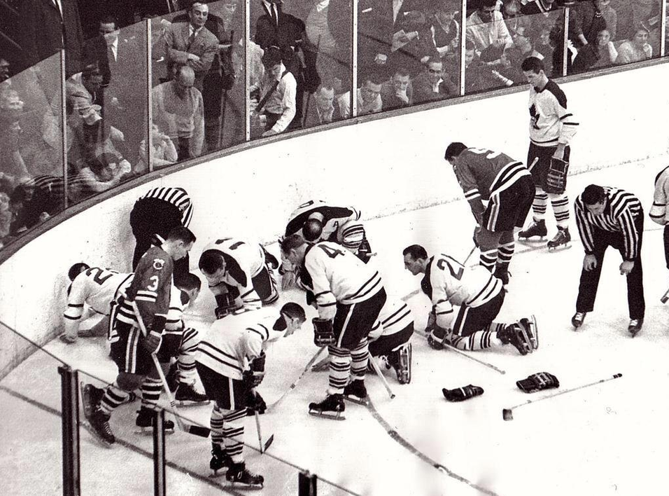 Blackhawks and Maple Leafs players looking for a lost contact lense during a 1962 game